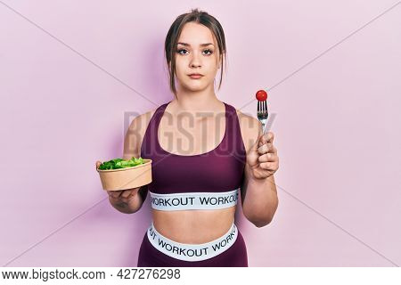 Young hispanic girl wearing sportswear eating salad relaxed with serious expression on face. simple and natural looking at the camera.