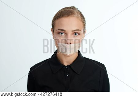 Portrait Of Sad Woman With Sealed Mouth On White Studio Background. Violence Theme