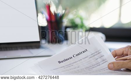Focus On Hand. Businessman Holding Paper Of Business Contract And Working At Home With Computer Lapt