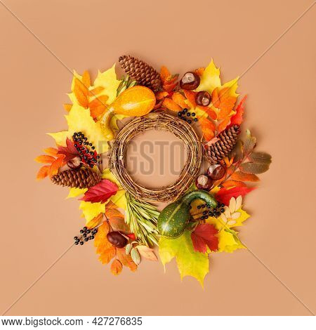 Autumn Wreath From Dry Colored Leaves, Cones, Pumpkins Squash, Black Berries On Beige Background, Co