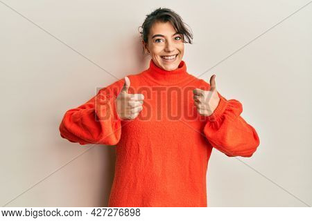 Young hispanic woman wearing casual winter sweater success sign doing positive gesture with hand, thumbs up smiling and happy. cheerful expression and winner gesture.
