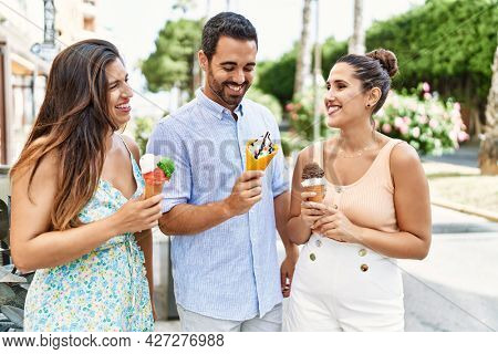 Three hispanic friends smiling happy eating ice cream at the city.