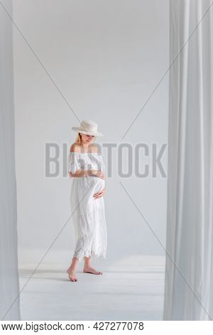 Young Pregnant Woman In Anticipation Of A Baby In A White Hat, Dress, Hugs Her Belly. Tender Blonde