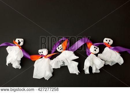 Decoration For Halloween Party - Ghosts From Paper Napkin And Violet Purple Tape On Black Background