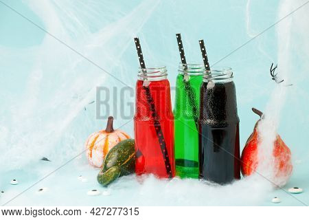 Halloween Drink. Black Red Green Cocktail In Glass Jar Decorated With  Straws, Pupmkins On Blue, Cre