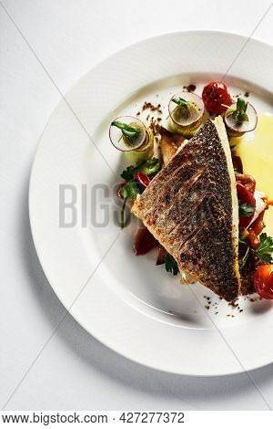 Grilled Sea Bass With Fried Tomatoes, Served With Potatoes. Fish Dish Top View, Light Background, Co