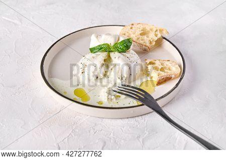 Italian Cut Burrata Cheese With Ciabatta Bread And Olive Oil On White Plate With Black Fork. Close U