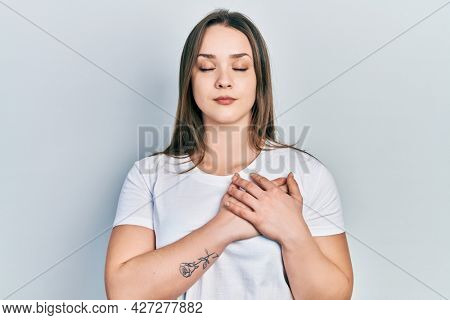 Young hispanic girl wearing casual white t shirt smiling with hands on chest, eyes closed with grateful gesture on face. health concept.