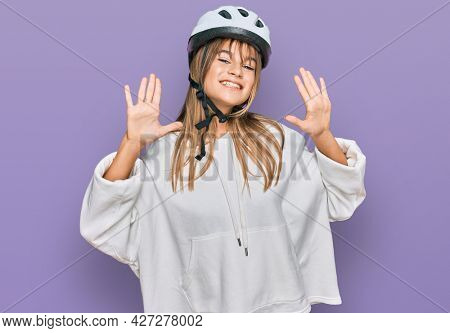 Teenager caucasian girl wearing bike helmet showing and pointing up with fingers number ten while smiling confident and happy.