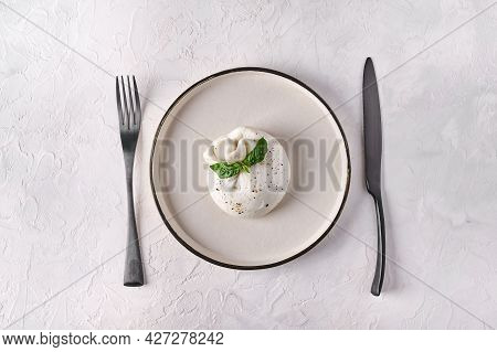 Italian Cheese Burrata With Basil On White Plate With Black Fork And Knife. Top View. Copy Space