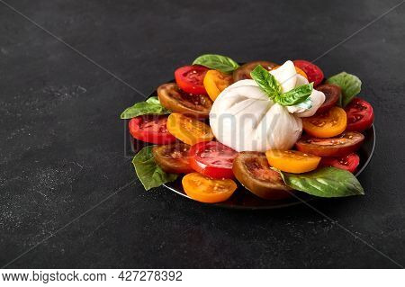Salad With Italian Burrata Cheese With Basil And Tomato On Dark Textured Background. Close Up