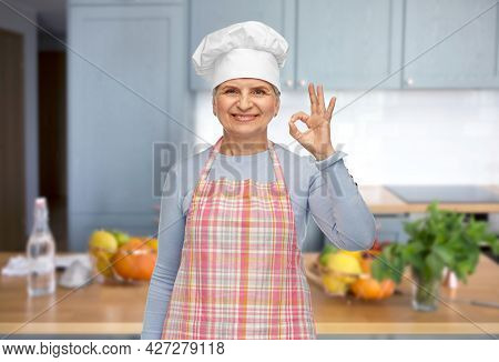 cooking, culinary and old people concept - portrait of smiling senior woman or chef in toque in apron showing ok hand sign over home kitchen background