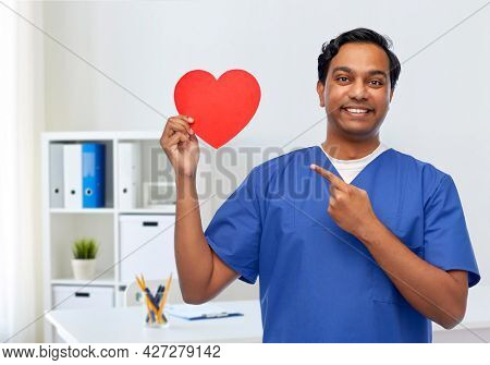 healthcare, profession and medicine concept - happy smiling indian doctor or male nurse in blue uniform with red heart over medical office at hospital background
