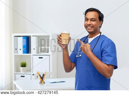 healthcare, profession and medicine concept - happy smiling indian doctor or male nurse in blue uniform with takeaway coffee cup and stethoscope over medical office at hospital background