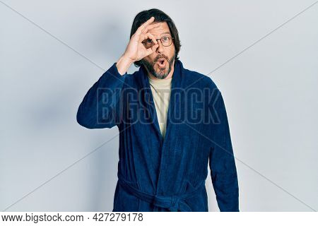 Middle age caucasian man wearing bathrobe and glasses doing ok gesture shocked with surprised face, eye looking through fingers. unbelieving expression.