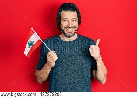 Middle age caucasian man holding lebanon flag smiling happy and positive, thumb up doing excellent and approval sign