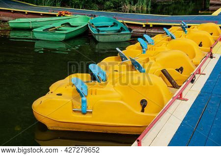 Yellow Pedal Boats Are Tied To The Dock. Boat Station On The Lake.