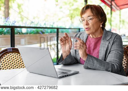 Serious 60-years-old Woman Is Online Working At Summer Cafe. She Sitting In Front Of Laptop Monitor