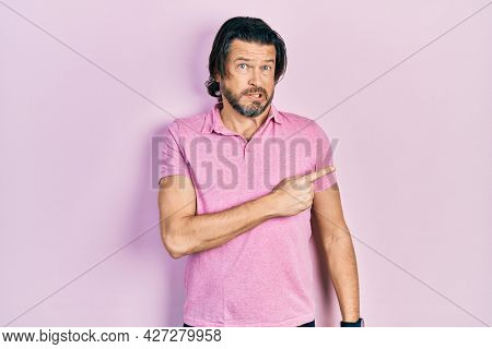 Middle age caucasian man wearing casual white t shirt pointing aside worried and nervous with forefinger, concerned and surprised expression