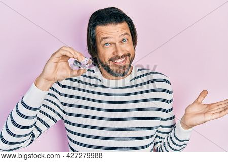Middle age caucasian man holding brilliant diamond stone celebrating achievement with happy smile and winner expression with raised hand