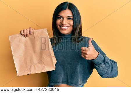 Young latin transsexual transgender woman holding take away paper bag smiling happy and positive, thumb up doing excellent and approval sign