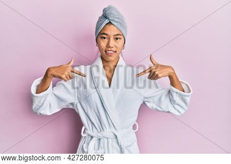 Young chinese woman wearing shower towel cap and bathrobe looking confident with smile on face, pointing oneself with fingers proud and happy.