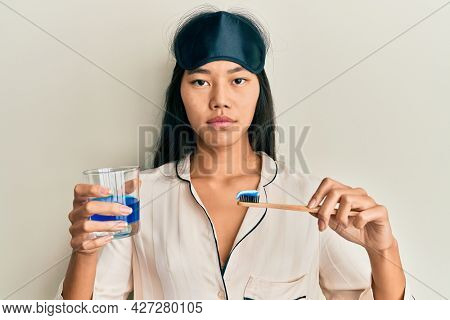 Young chinese woman wearing pajama using toothbrush and mouthwash relaxed with serious expression on face. simple and natural looking at the camera.