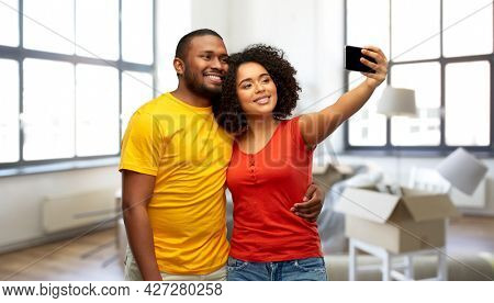 moving, real estate and people concept - happy smiling african american couple taking selfie by smartphone over new home background