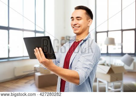 moving, real estate and people concept - happy young man tablet computer over new home background