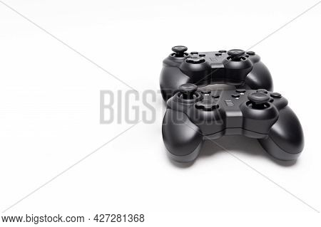 Two Generic Black Gaming Controllers. Isolated On White Background. Copy Space.