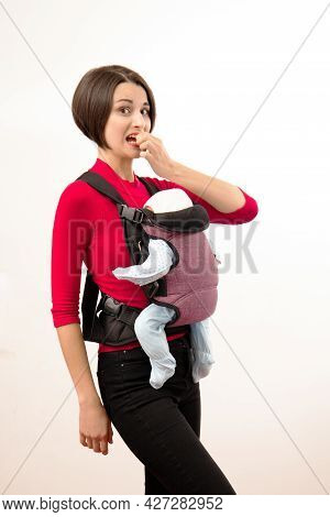 Babywearing Confused Young Mother With Baby In Not Ergonomic Carrier. Isolated On White.