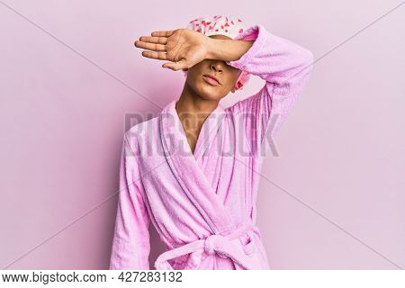 Hispanic man wearing make up wearing shower towel cap and bathrobe covering eyes with arm, looking serious and sad. sightless, hiding and rejection concept