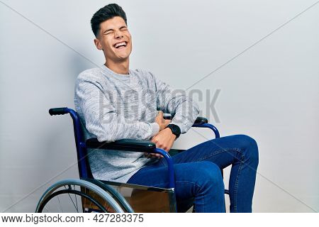 Young hispanic man sitting on wheelchair smiling and laughing hard out loud because funny crazy joke with hands on body.