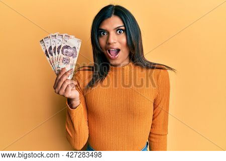 Young latin transsexual transgender woman holding 500 mexican pesos banknotes scared and amazed with open mouth for surprise, disbelief face