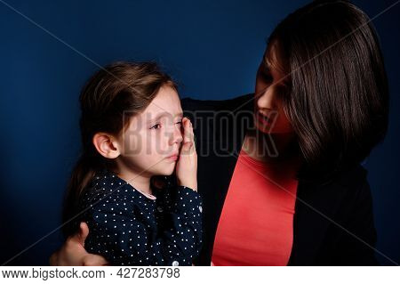 Young Mother Holding Her Crying Kid Girl On Dark Blue Background.