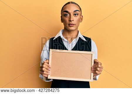 Hispanic man wearing make up and long hair holding empty corkboard relaxed with serious expression on face. simple and natural looking at the camera.