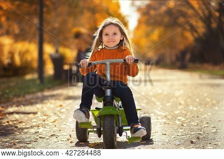 Portrait Of A Little Happy Girl On A Bike In The Morning Autumn Park.