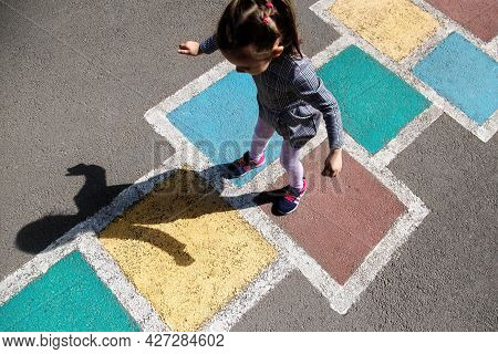 Kid Girl 4 Y.o. Playing Hopscotch On Playground Outdoors.