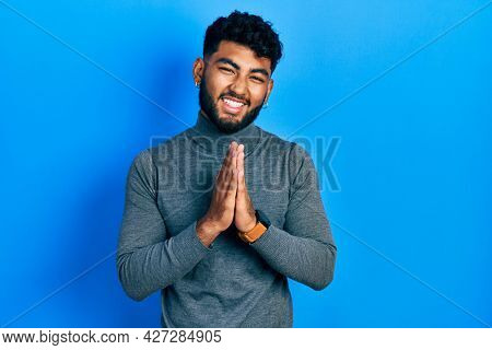 Arab man with beard wearing turtleneck sweater praying with hands together asking for forgiveness smiling confident.