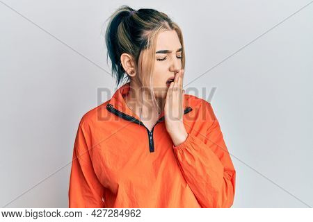 Young modern girl wearing sports sweatshirt bored yawning tired covering mouth with hand. restless and sleepiness.