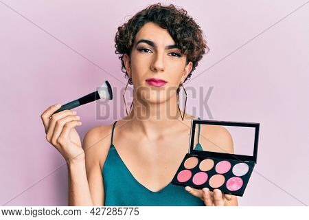 Young man wearing woman make up holding makeup brush and blush relaxed with serious expression on face. simple and natural looking at the camera.
