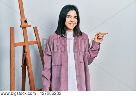 Young brunette woman standing by empty easel stand smiling happy pointing with hand and finger to the side