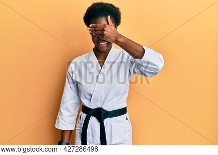 Young african american girl wearing karate kimono and black belt smiling and laughing with hand on face covering eyes for surprise. blind concept.