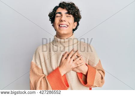 Hispanic young man wearing casual winter sweater smiling with hands on chest with closed eyes and grateful gesture on face. health concept.