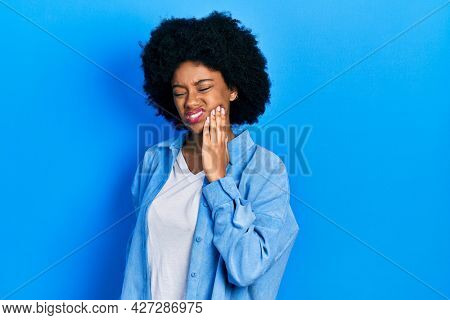 Young african american woman wearing casual clothes touching mouth with hand with painful expression because of toothache or dental illness on teeth. dentist