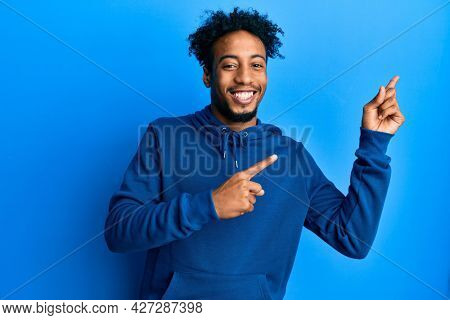 Young african american man with beard wearing casual sweatshirt smiling and looking at the camera pointing with two hands and fingers to the side.