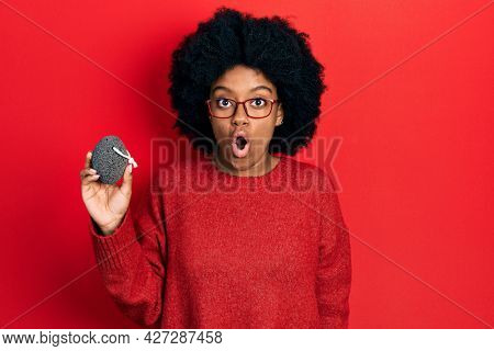 Young african american woman holding pumice stone scared and amazed with open mouth for surprise, disbelief face