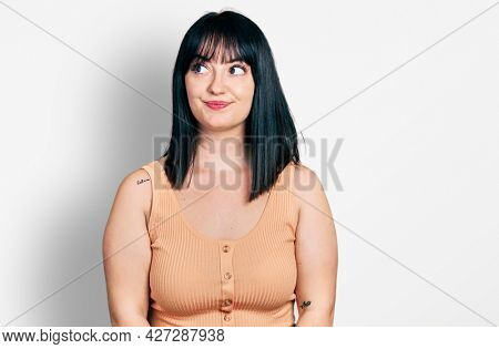 Young hispanic plus size woman wearing casual clothes smiling looking to the side and staring away thinking.