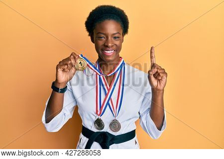 Young african american girl wearing karate kimono and black belt smiling with an idea or question pointing finger with happy face, number one