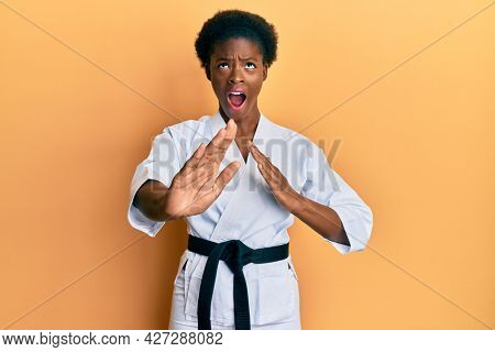 Young african american girl wearing karate kimono and black belt angry and mad screaming frustrated and furious, shouting with anger looking up.